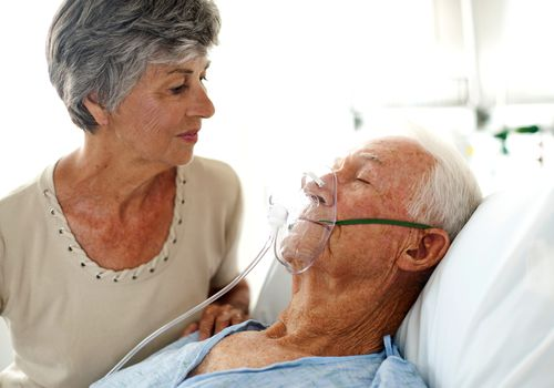 Elderly woman looking at her husband wearing an oxygen mask