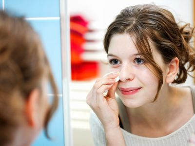 teenage girl looking at herself in the mirror cleaning her face