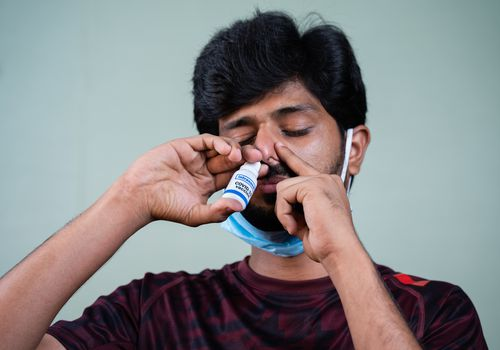 man spraying intranasal COVID vaccine up nose