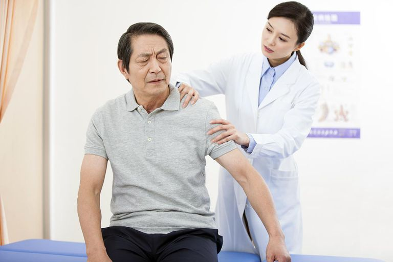 A PT examines a patient's shoulder.