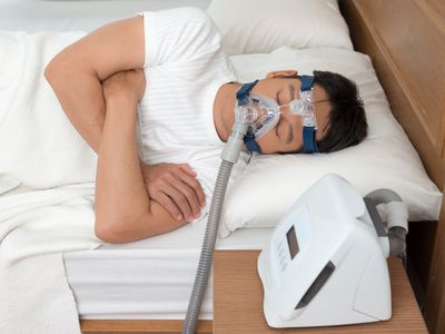 Man Wearing Cpap Mask While Suffering From Sleep Apnea On Bed At Home