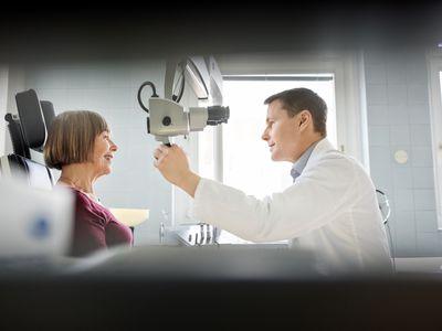 Otolaryngologist checking sore throat of senior patient