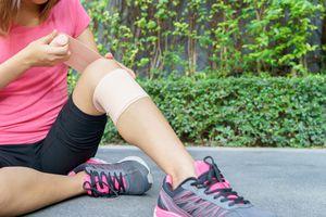 woman applying elastic bandage to knee joint