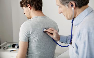 Doctor listening to patients lungs