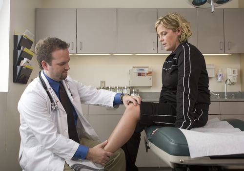 male doctor examining female patient's leg