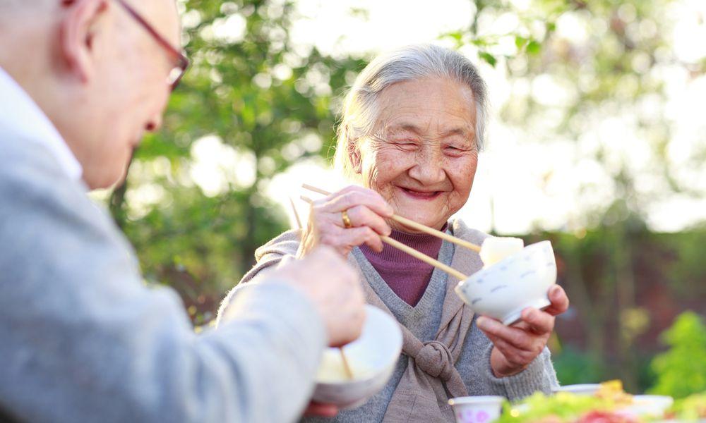 An elderly couple shares a meal.
