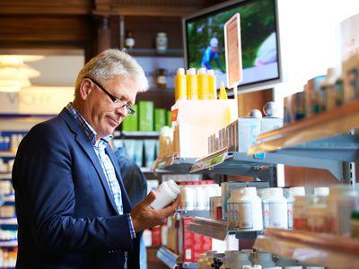 man checking pill bottles