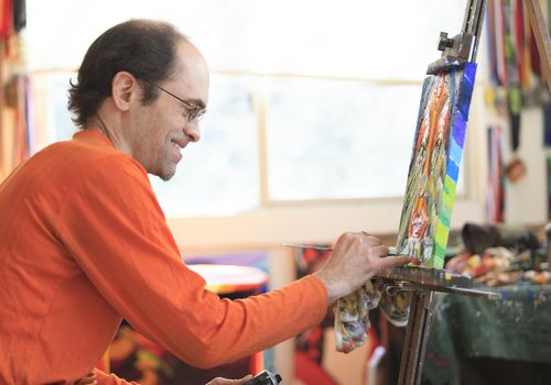 man with aspergers painting in his studio