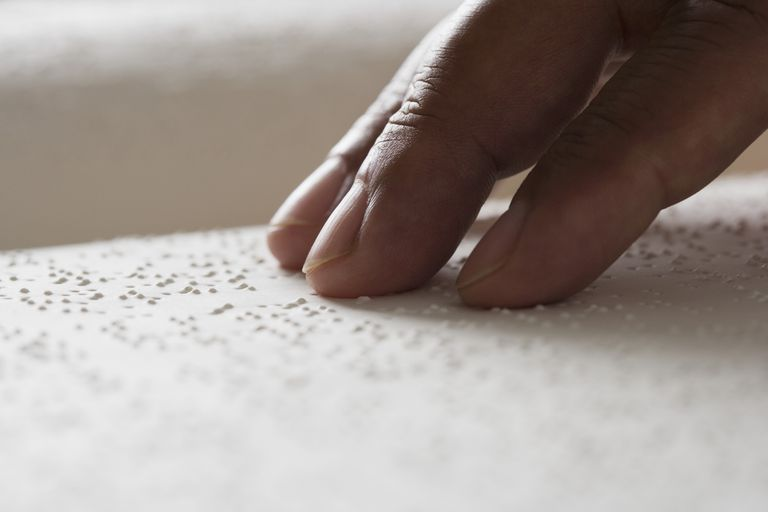 Close up of person's fingers on braille