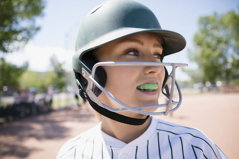 Softball player with mouthguard and helmet