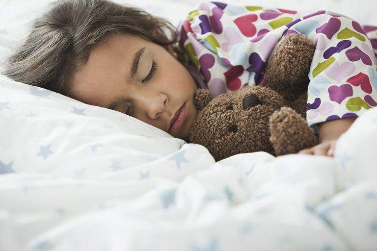 Girl sleeping with a teddy bear