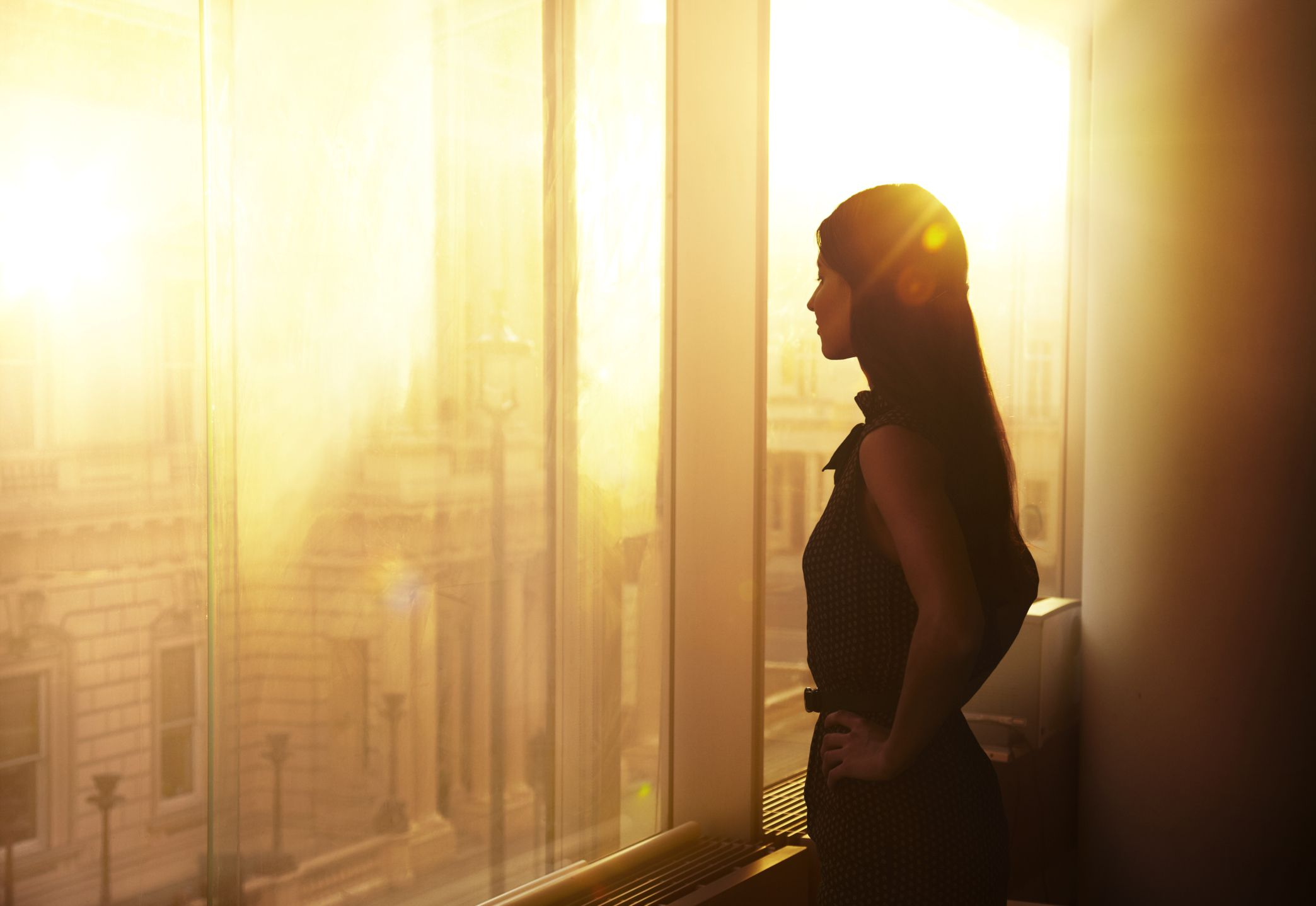 Woman looking over the city at sunrise.