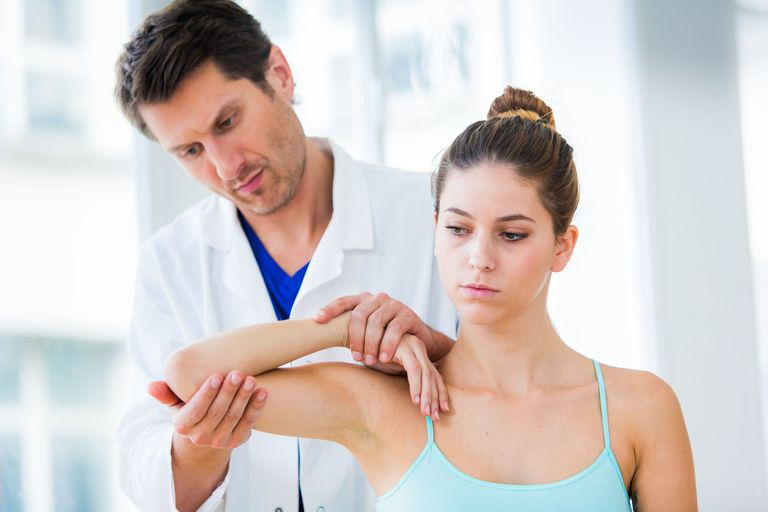 Medical consultation Doctor examining elbow's woman.