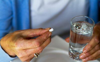 Older woman taking cardiac medication.