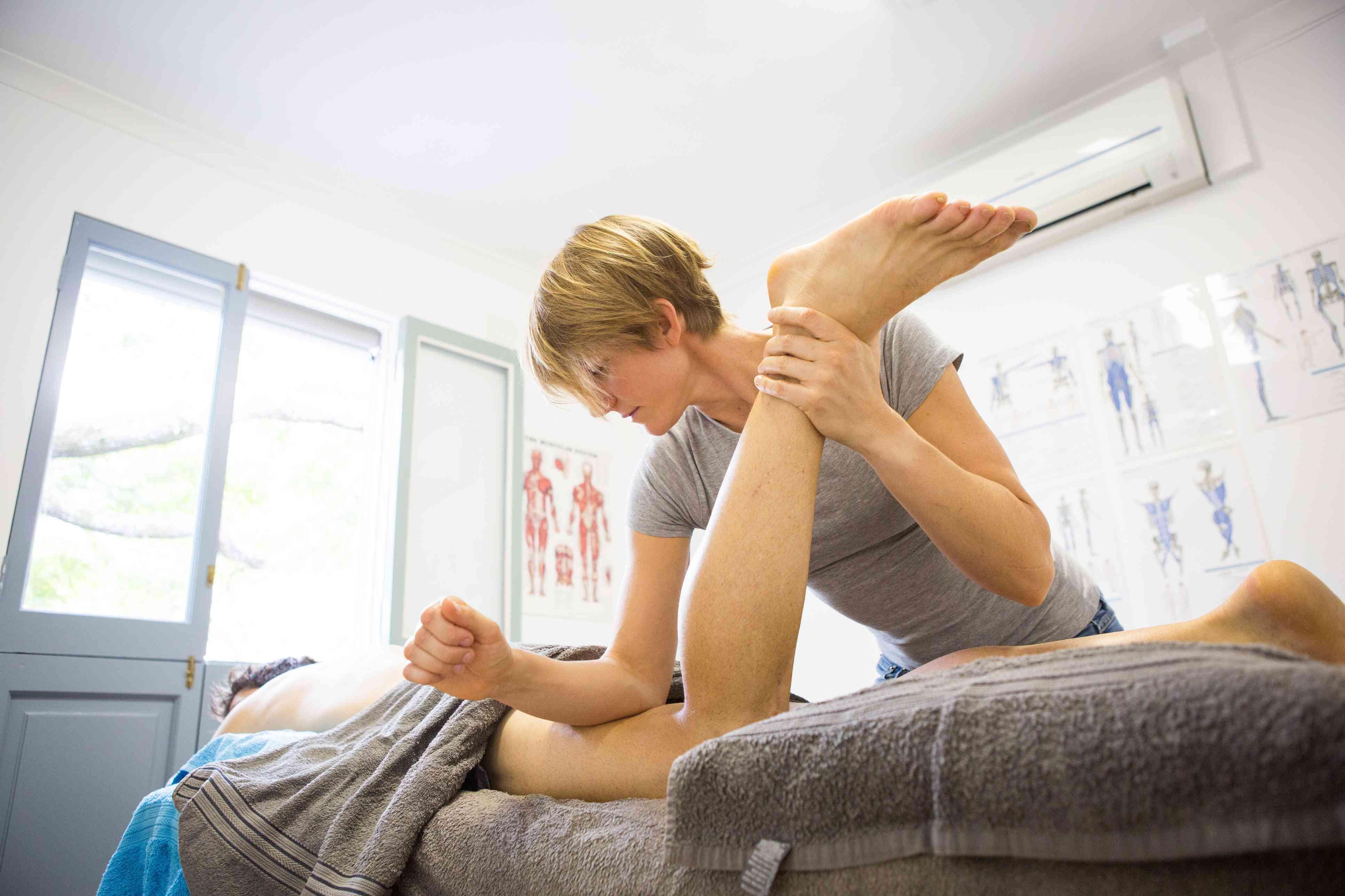 Sports massage therapist working on a patient's leg