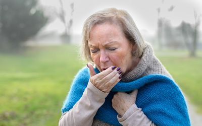 Senior Woman Coughing While Standing On Field During Foggy Winter