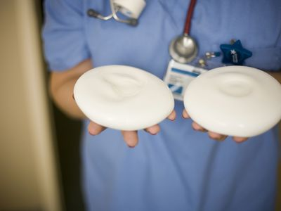 Female healthcare worker holding breast implants
