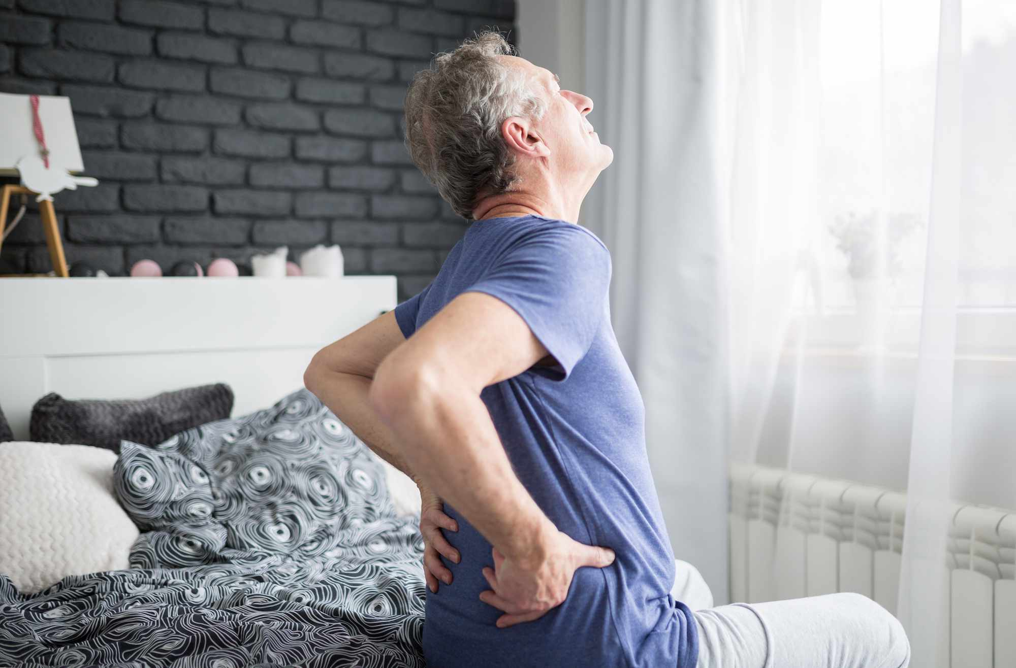A man sitting on his bed with low back pain