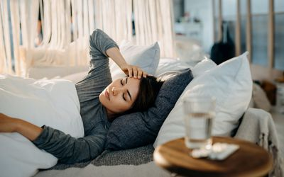 Young Asian woman lying in bed and feeling sick, with a glass of water and medicine on the side table