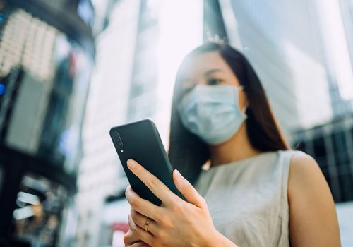 Young Asian businesswoman with protective face mask to protect from viruses/air pollution, using smartphone while commuting in the city, against energetic and prosperous downtown city street with urban skyscrapers