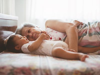 Grandmother lying in bed with baby