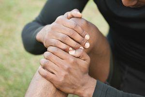 Man holding injured knee, cropped