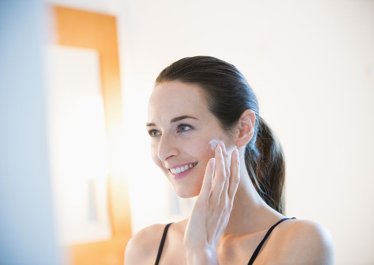 Smiling woman applying face cream to cheek