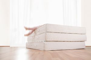 Person jumping back-down on three mattresses stacked on a wood floor