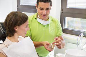 Poorly fitting dentures. Dentist showing woman dentures