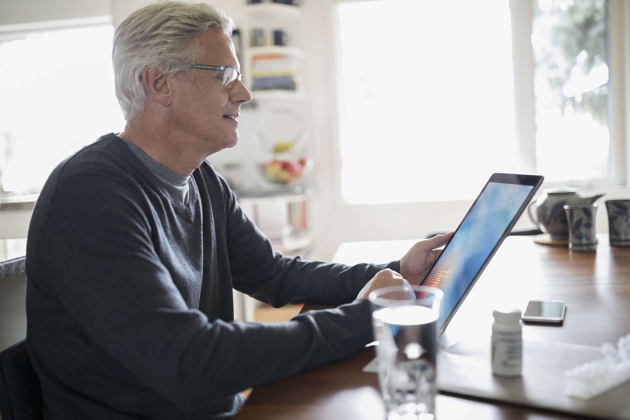 A man using his tablet at the dining room table