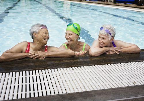 Three older ladies laughing during swim class