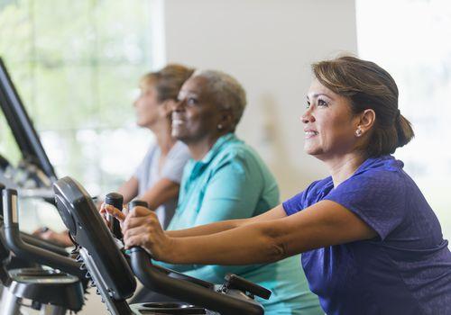 Multiracial women riding exercise bikes at gym