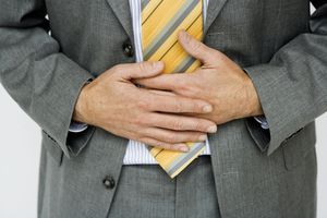 Man in suit and tie holding stomach