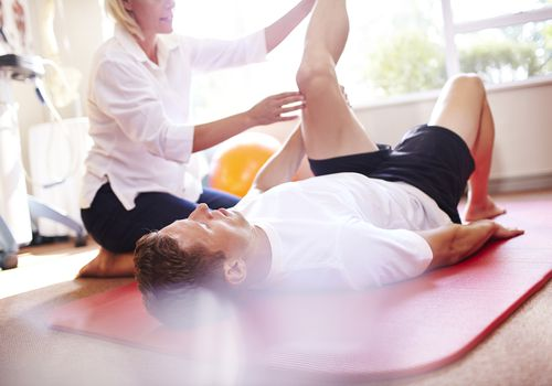 Physical therapist stretches man's leg