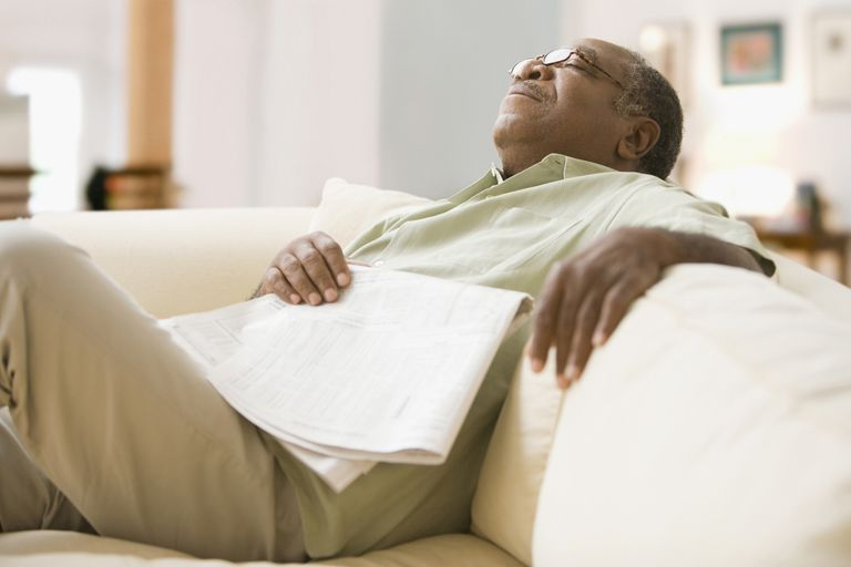 Senior African man sleeping on sofa with newspaper