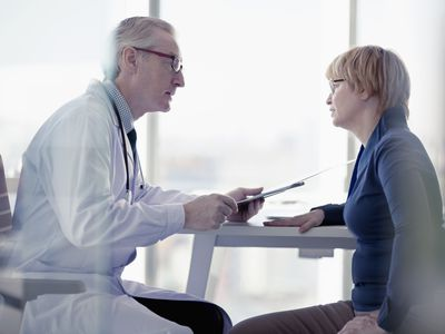 Doctor talking to woman patient in his office