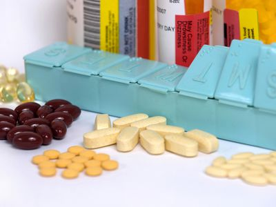 Several pills in front of a pill organizer and prescription bottles