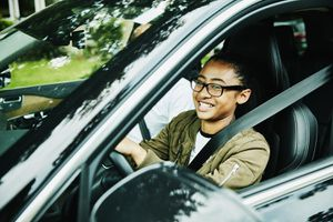 Laughing young woman in drivers seat of car taking driving lesson from father