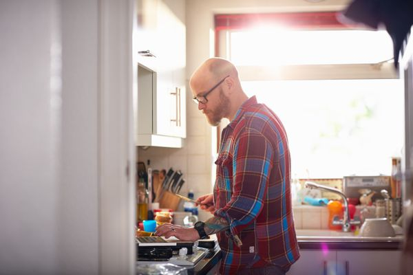 Man in kitchen using laptop whilst making lunch