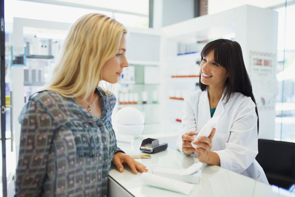 Woman discussing product with pharmacist in drugstore