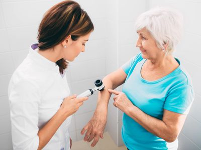 Female dermatologist Inspecting patient skin moles at clinic