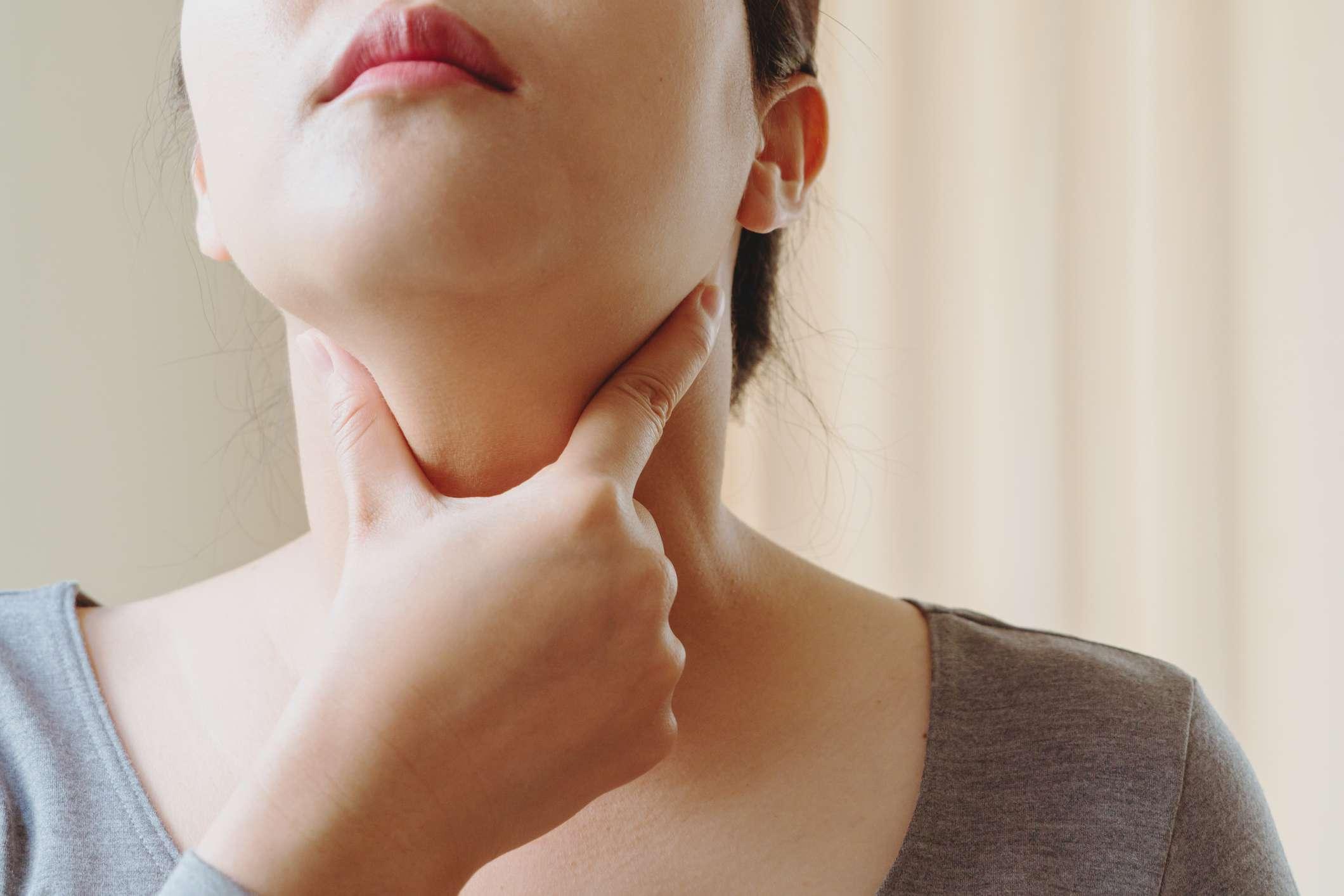 Woman performing a thyroid gland test