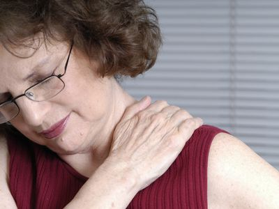 Woman clutching her shoulder from muscle strain