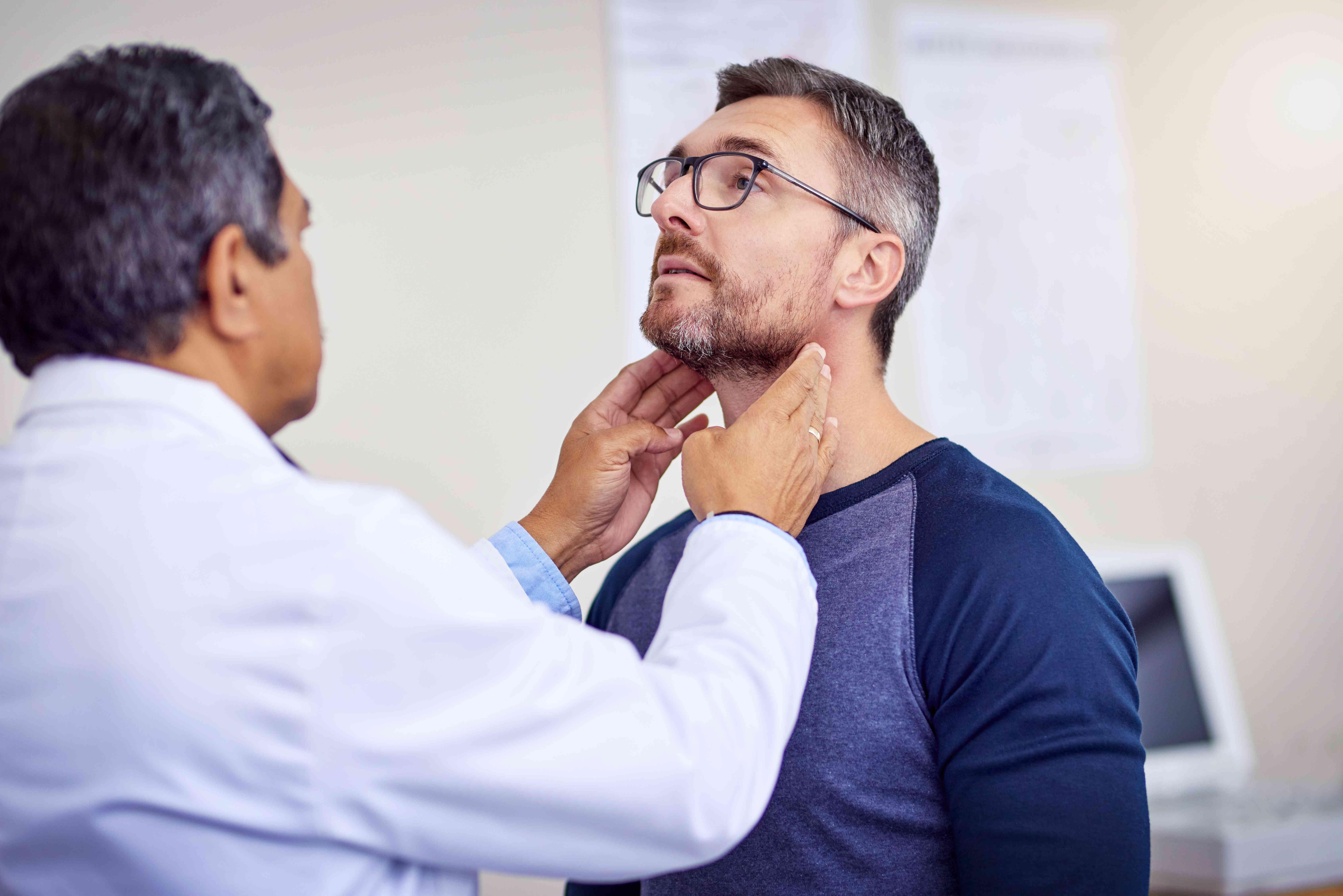 Doctor examining a man's neck