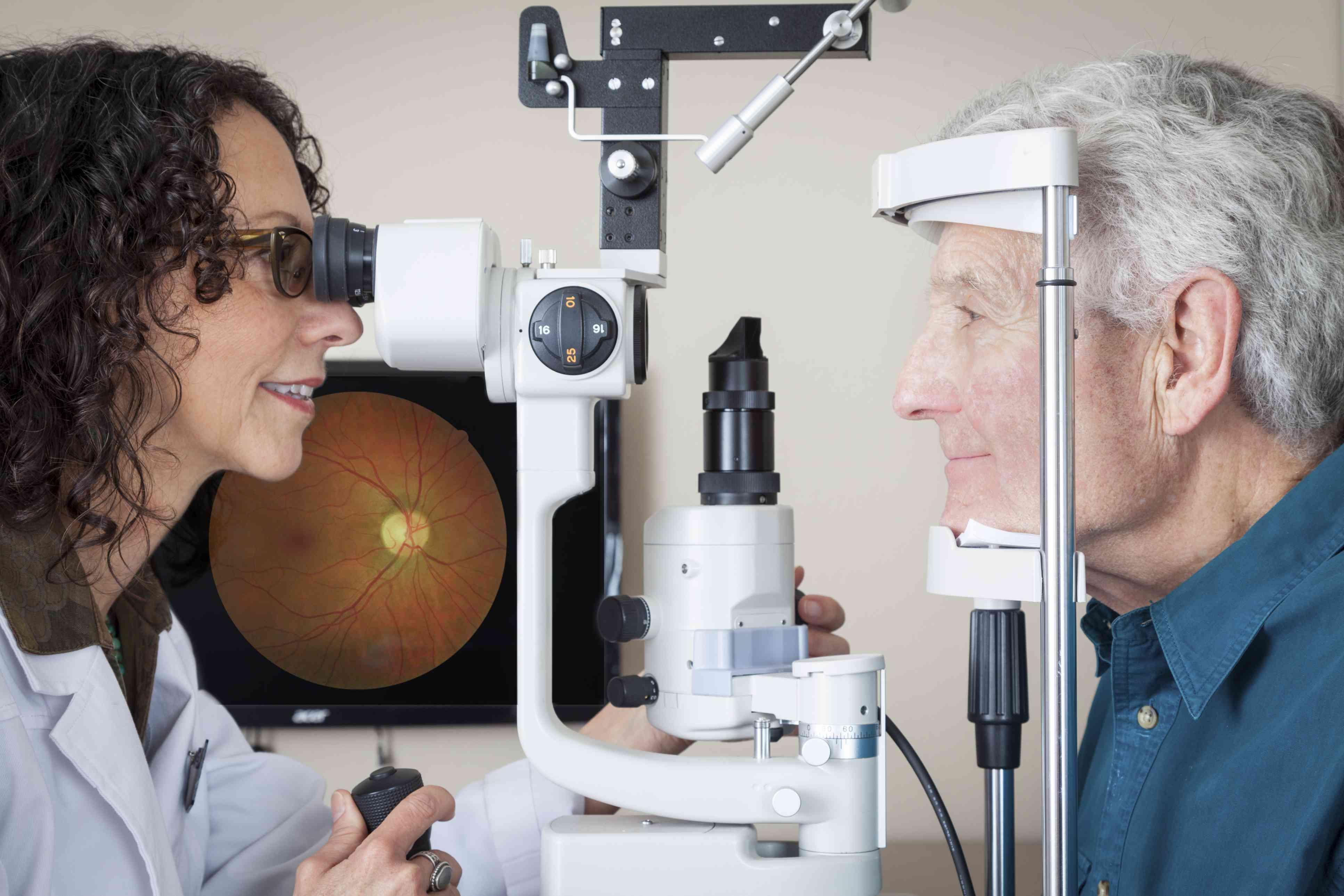 Doctor performing eye exam on elderly man