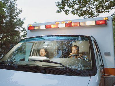 Male and female paramedics in cab of ambulance
