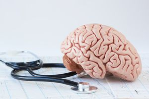 Human brain model and stethoscope on background of brain waves f
