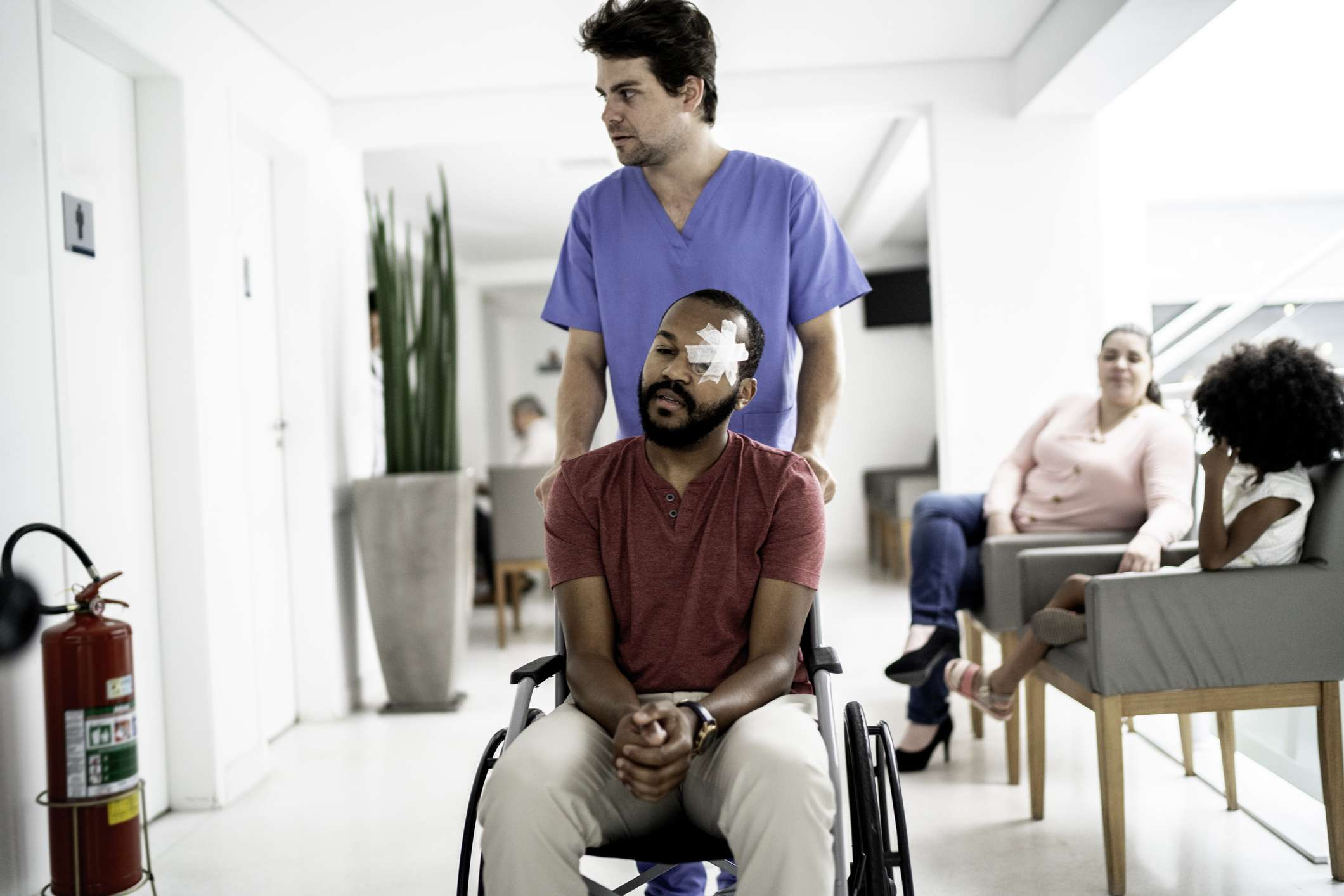 Nurse walking with wheelchair patient after eye surgery - stock photo