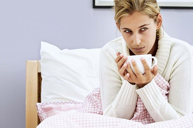 woman sitting in bed with a cup of soup