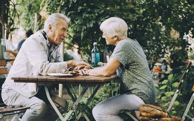 Senior couple holding hands talking while sitting at restaurant in city